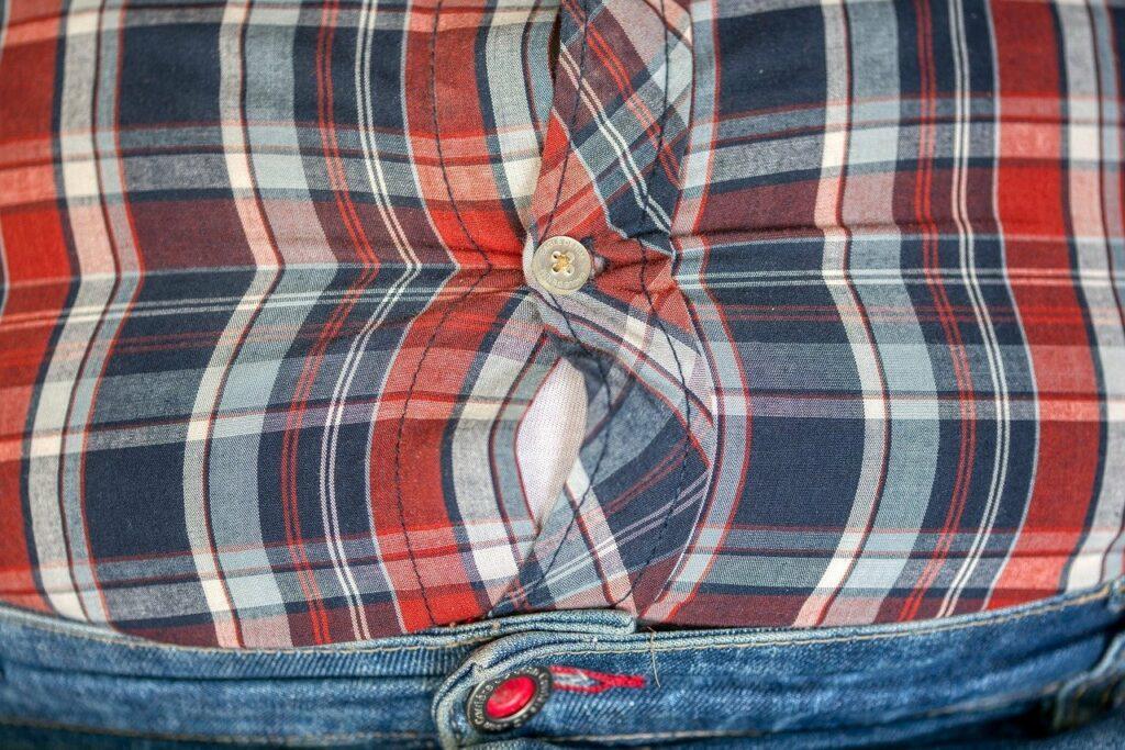 Männerbauch spannt das Hemd